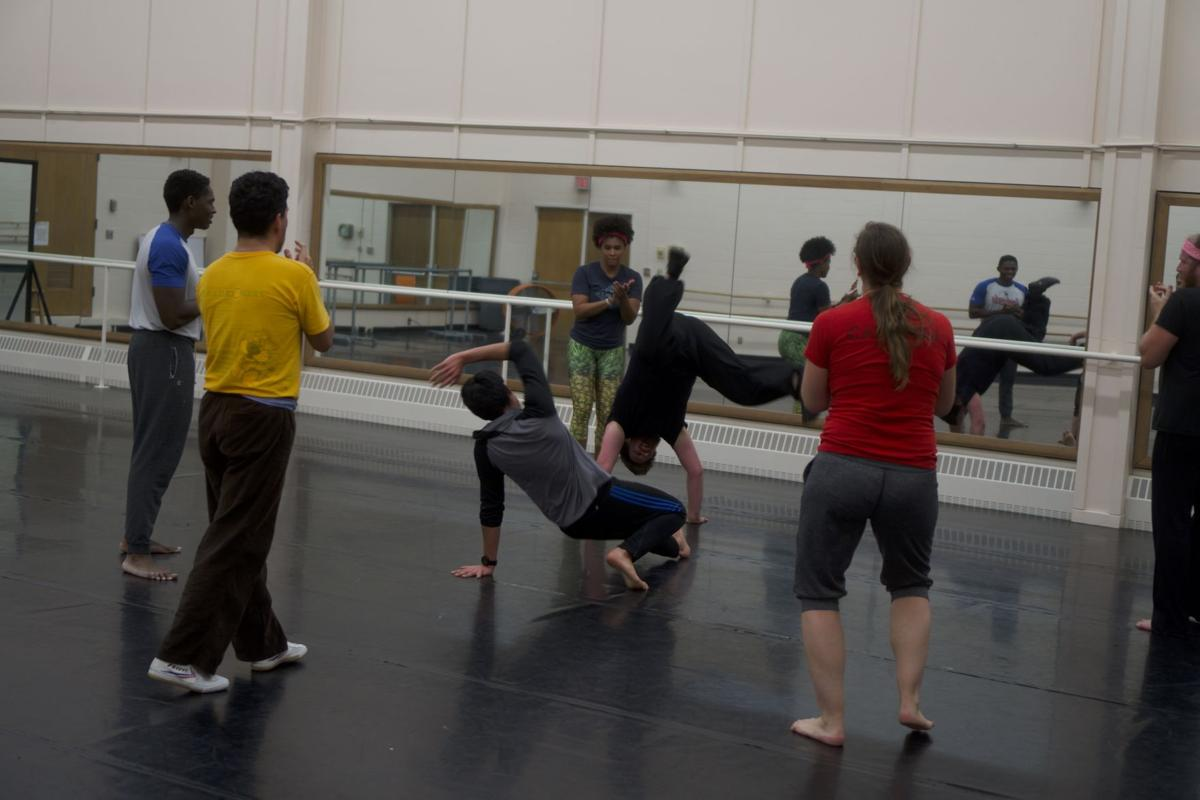 Two men spar as they practice Capoeira. They are surrounded by 4 spectators who cheer them on