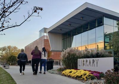 Lawrence residents walk up the sidewalk toward the entrance of the Lawrence public library