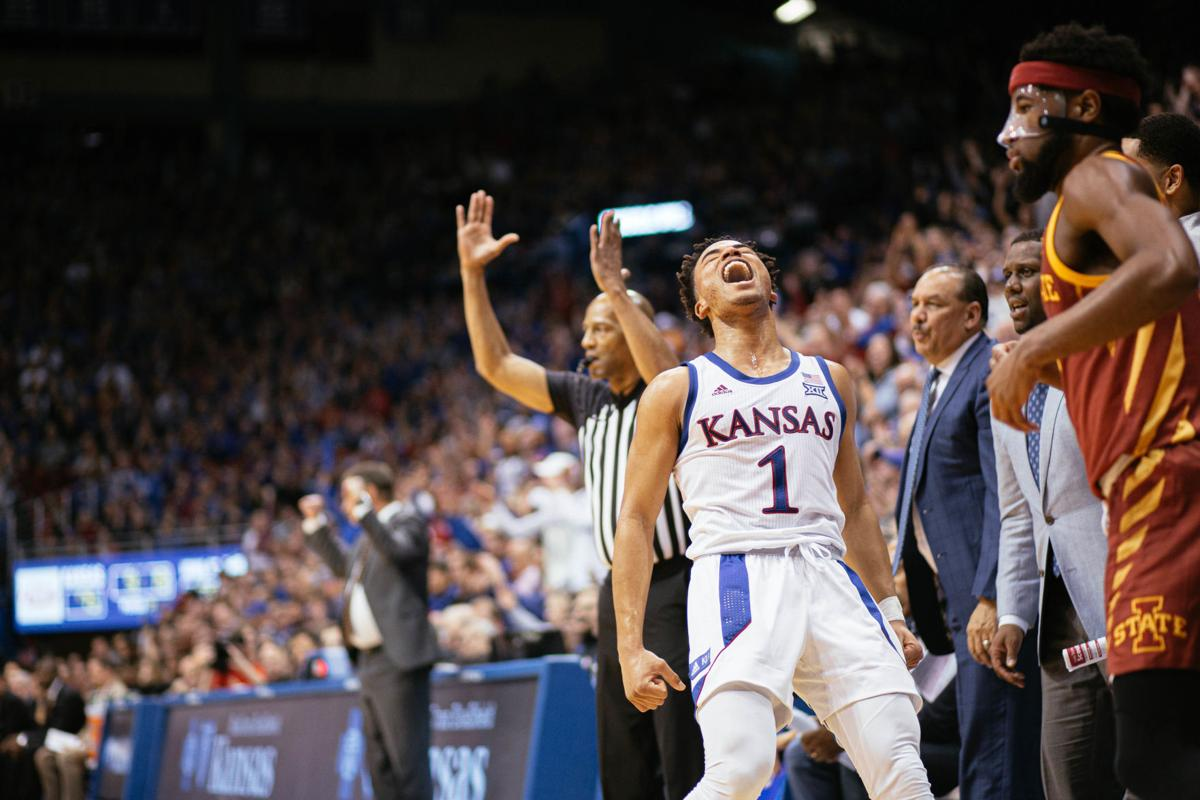 Devon Dotson stands on the sideline as he lifts his head in exclamation. A referee behind him throws both hands up