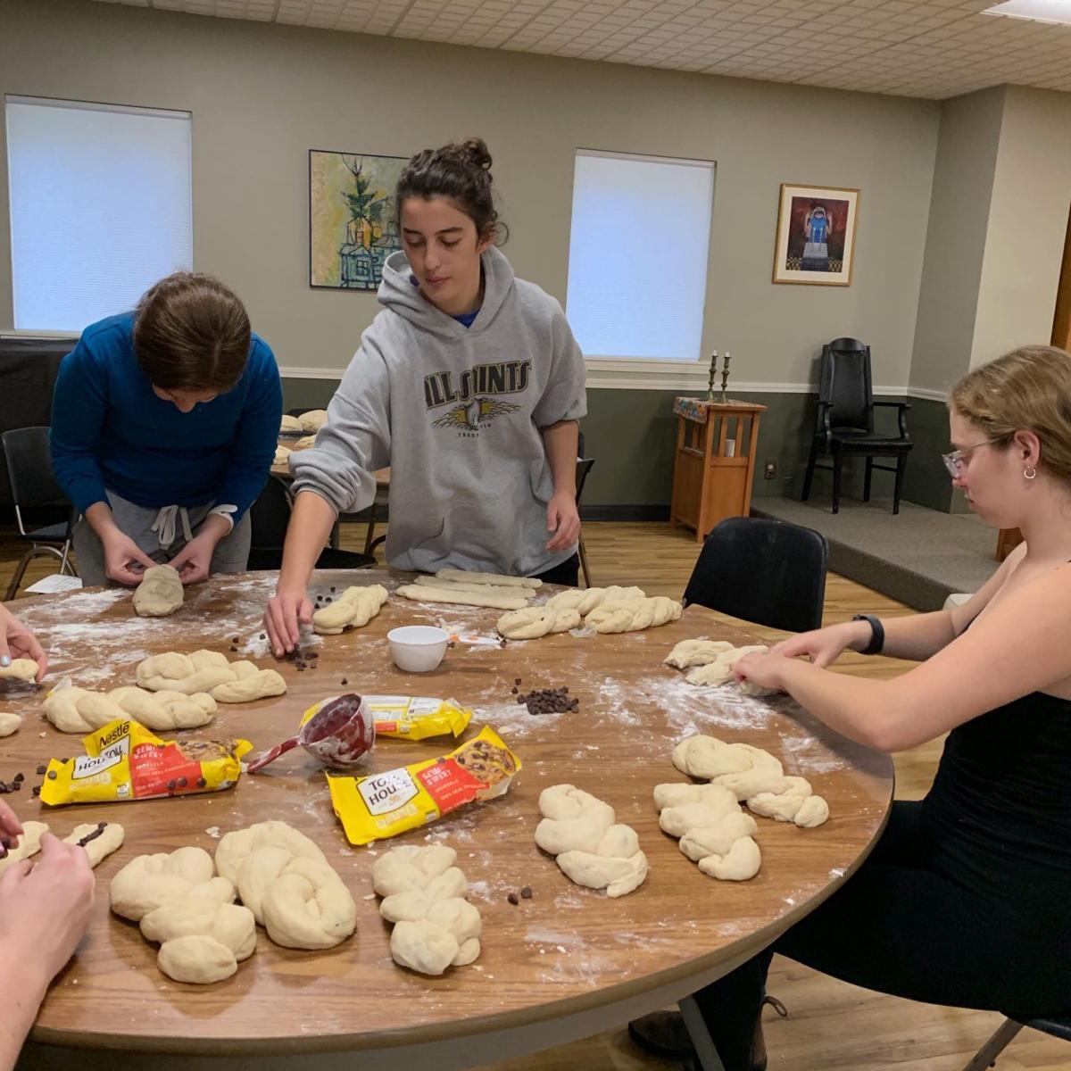 Four female K.U. students braid raw challah bread on a wooden table