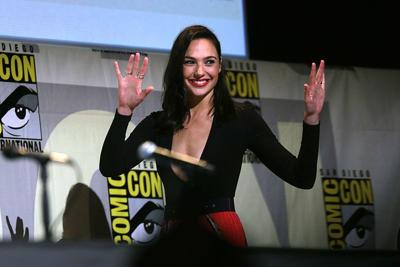 Gal Gadot holds her hands up and smiles on stage at Comic Con