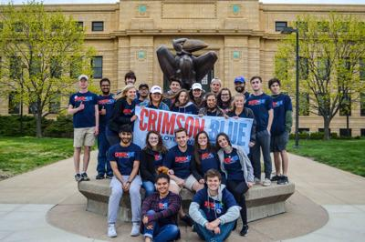 Crimson and Blue members pose in front of the Jayhawk Statue outside Strong Hall holding their campaign banner.