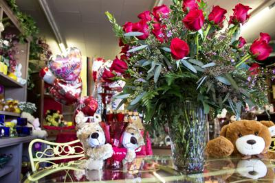 A bouquet of roses and several teddy bears sit on a counter