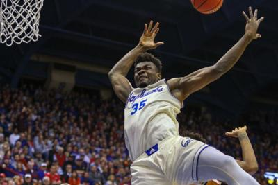 Senior center Udoka Azubuike jumps toward the basket and flails his arms to grab the ball
