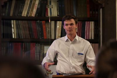 Seth Wingerter stands and speaks in front of a book case