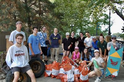 Students in the introductory sculpture class stand in front of bags of garbage they collected near the Kansas River