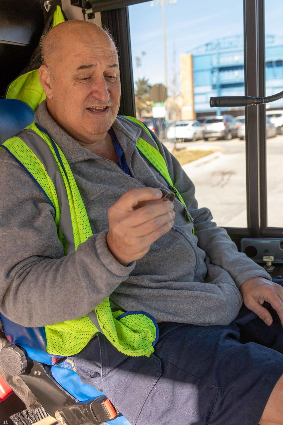 K.U. bus driver Rex Gardner performs a magic trick as he sits in his driver's seat