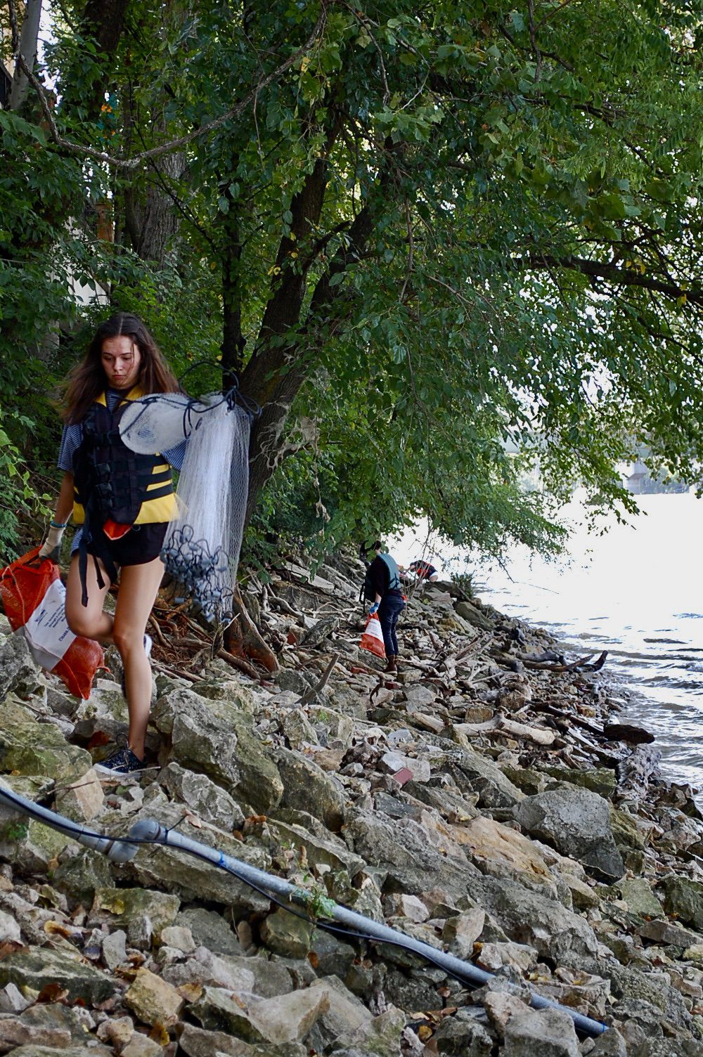 K.U. student Eleanor Walsh places trash in garbage bags as she walks on the bank of the Kansas River