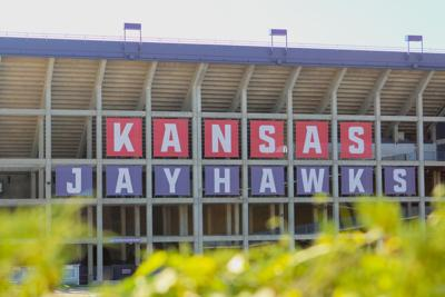 A sign saying Kansas Jayhawks hangs from the outside of Memorial Stadium