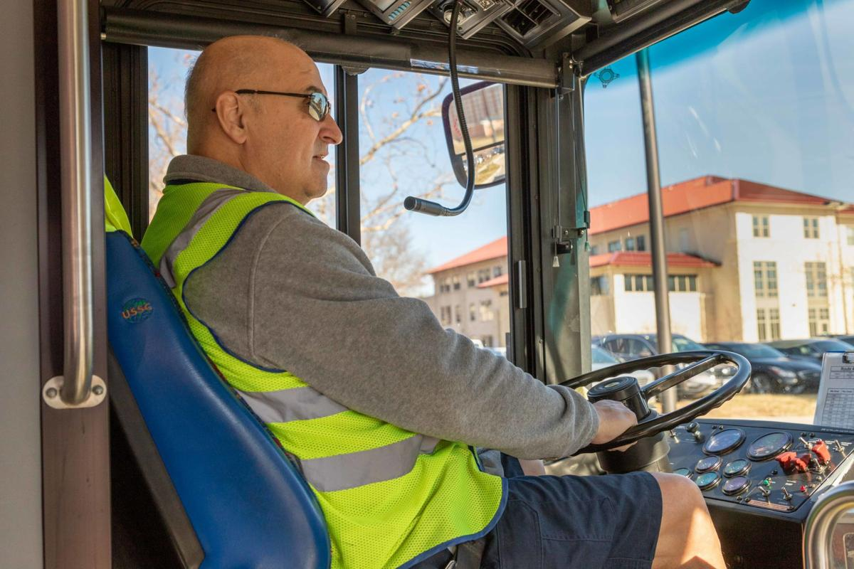 K.U. bus driver Rex Gardner sits in the driver's seat of his bus and looks at the road