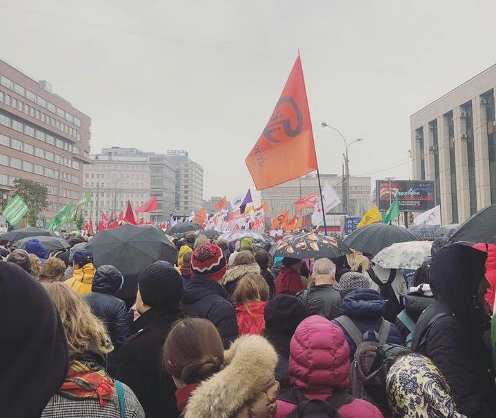 A crowd of Russian protesters march through the streets carrying flags