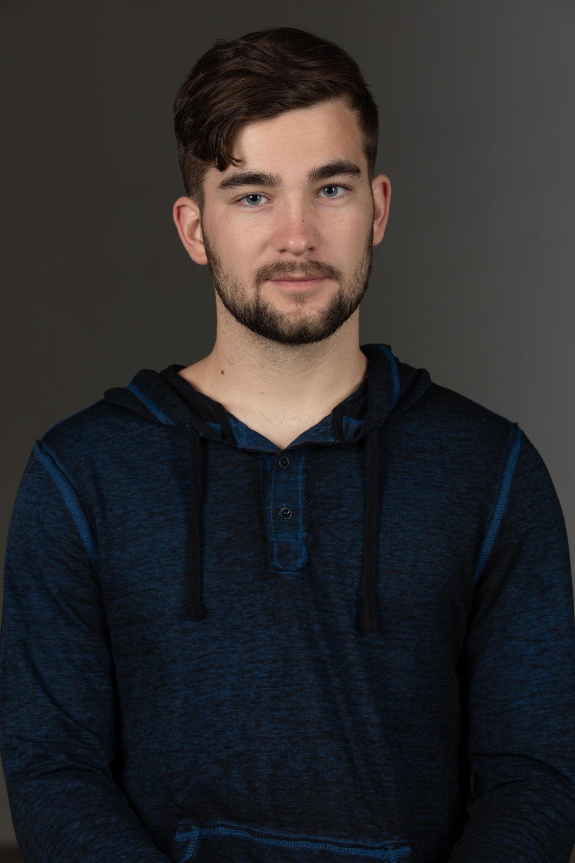 Josh McQuade smiles as he poses for a mugshot photo