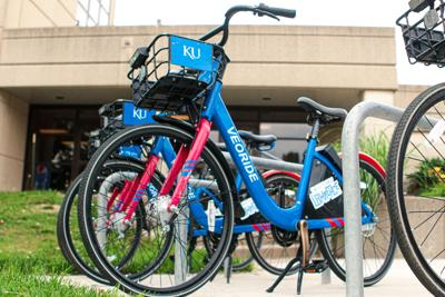 A VeoRide bike is parked among other bikes outside Green Hall