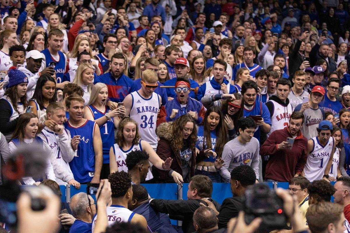 The crowd expresses shocked emotions as Bill Self separates his players during an altercation.