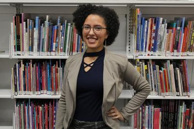 Alex Kimball-Williams stands and smiles as she poses for a photo in front of a wall of bookshelves