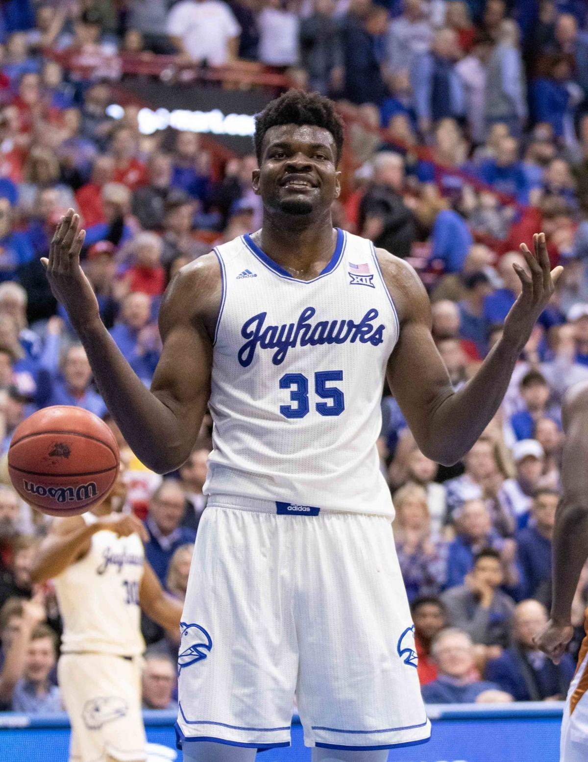 Brandishing a smile, Udoka Azubuike holds his hands in the air while the ball dribbles out to his side