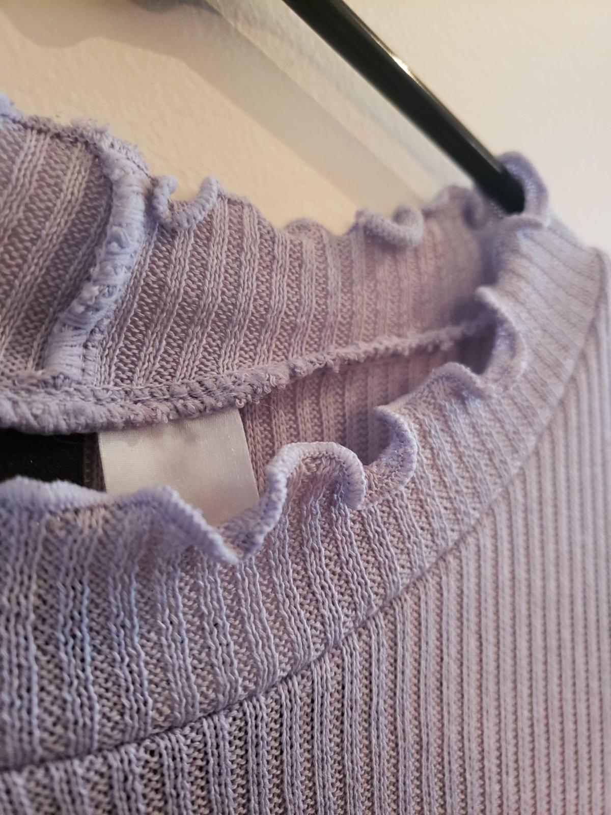 A long-sleeved top with a lettuce edge hem hangs on a hanger