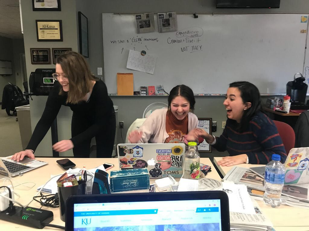 Savanna Smith, Nichola McDowell and Nicole Asbury laugh while sitting at a table in the newsroom of the UDK