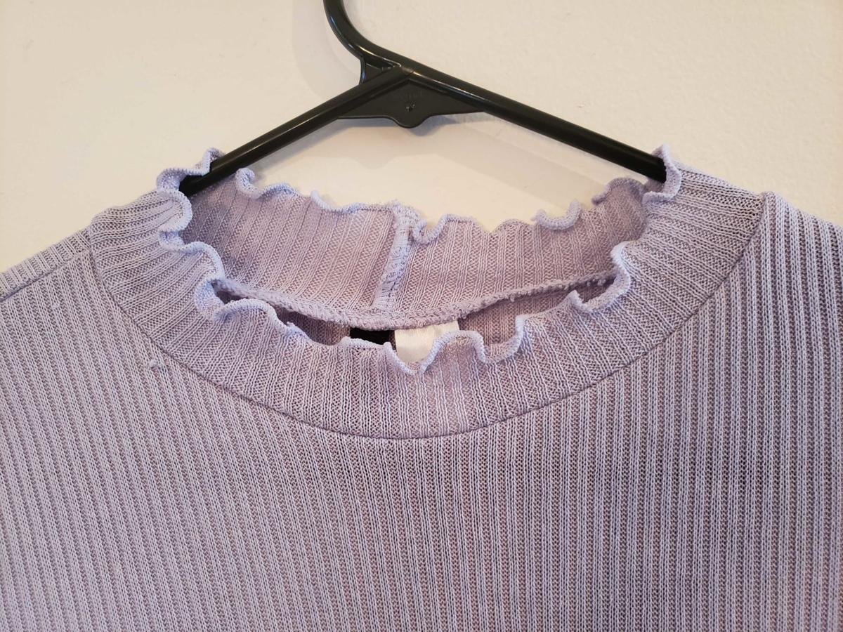 A long-sleeved top with lettuce edges hangs on a hanger