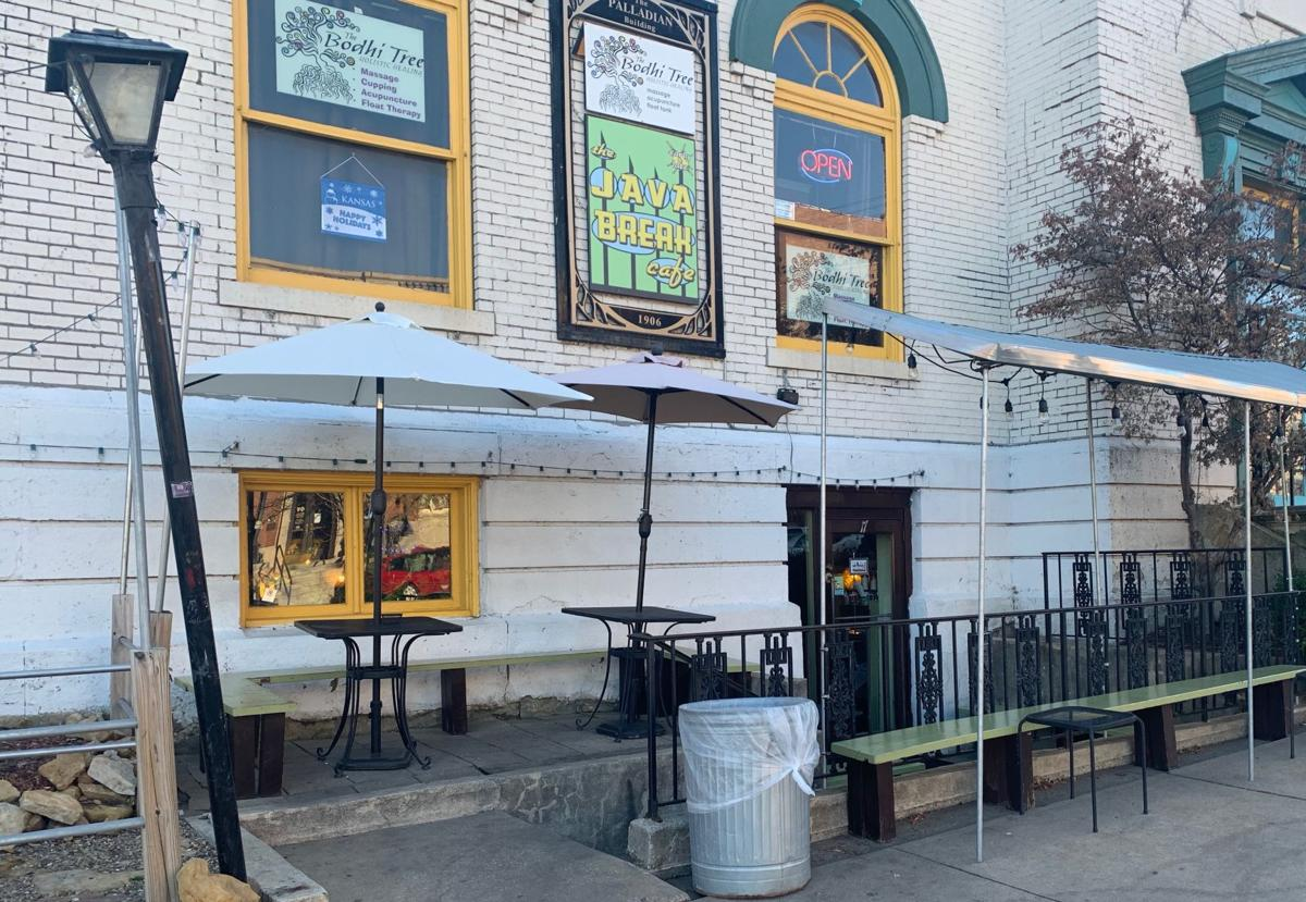The exterior of the Java Break coffee shop has two tables and a bench