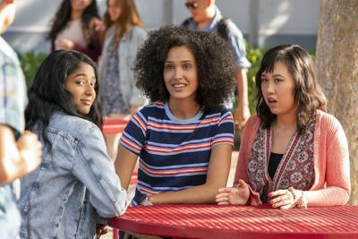 Three young women gather at a school lunch table and all stare at a person approaching them