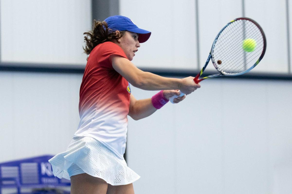 Vasiliki Karvouni jumps up to hit the ball with the racket in both hands