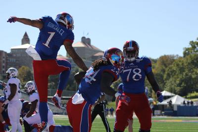 Taylor Martin, LaQuvionte Gonzalez and Hakeem Adeniji jump on the field celebrating a touchdown.