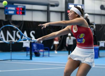 Luniuska Delgado extends both arms as she swings the racket up with her right hand toward the ball above her