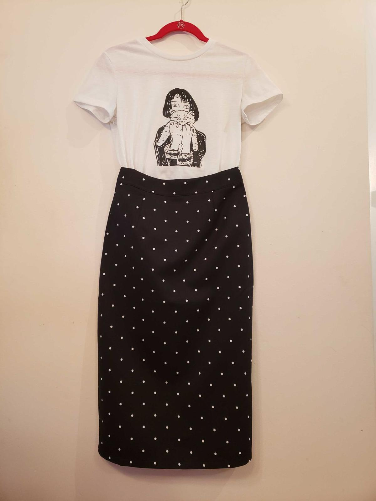 A short-sleeved t-shirt and a midi skirt hang on display