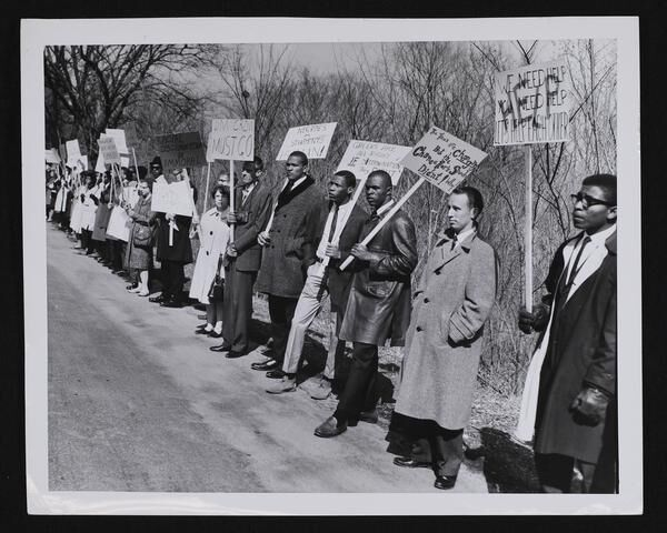 "Line of marchers including KU football players Michael Shinn and Gale Sayers; signs read ""Jim Crow Must Go"", ""Racial Discrimination is Immoral"""