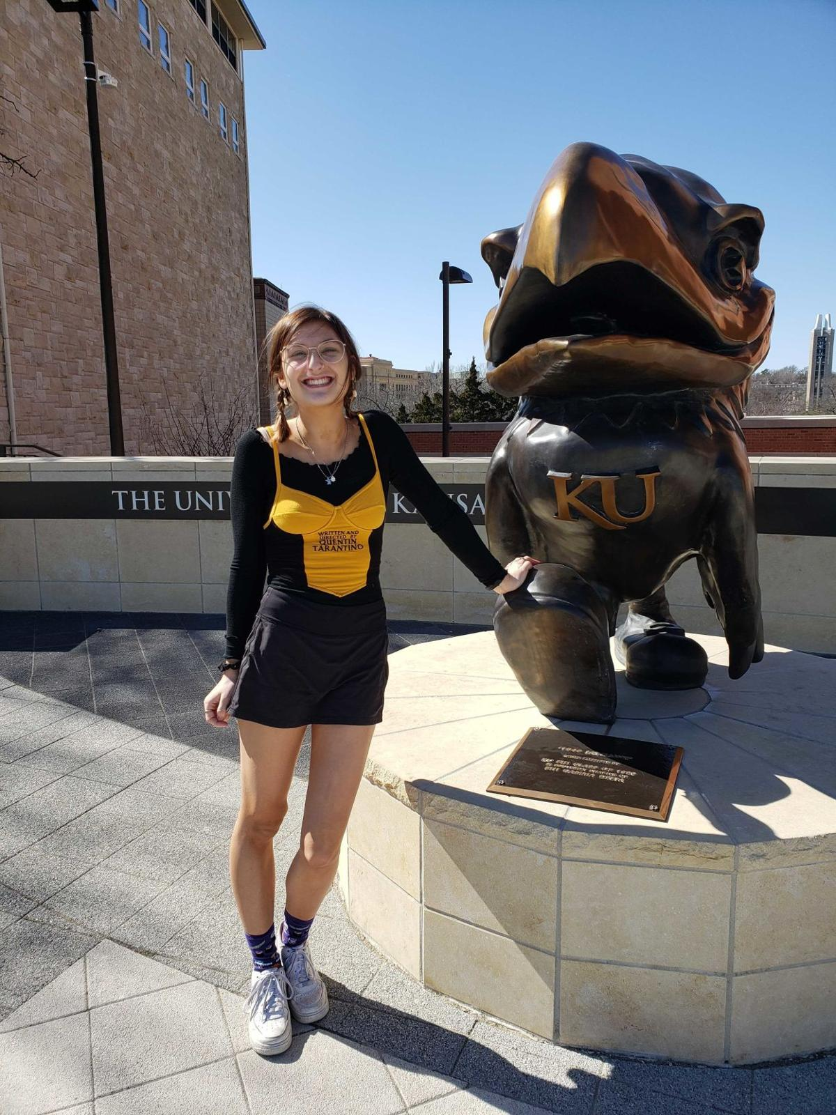 A woman stands next to a bronze Jayhawks statue