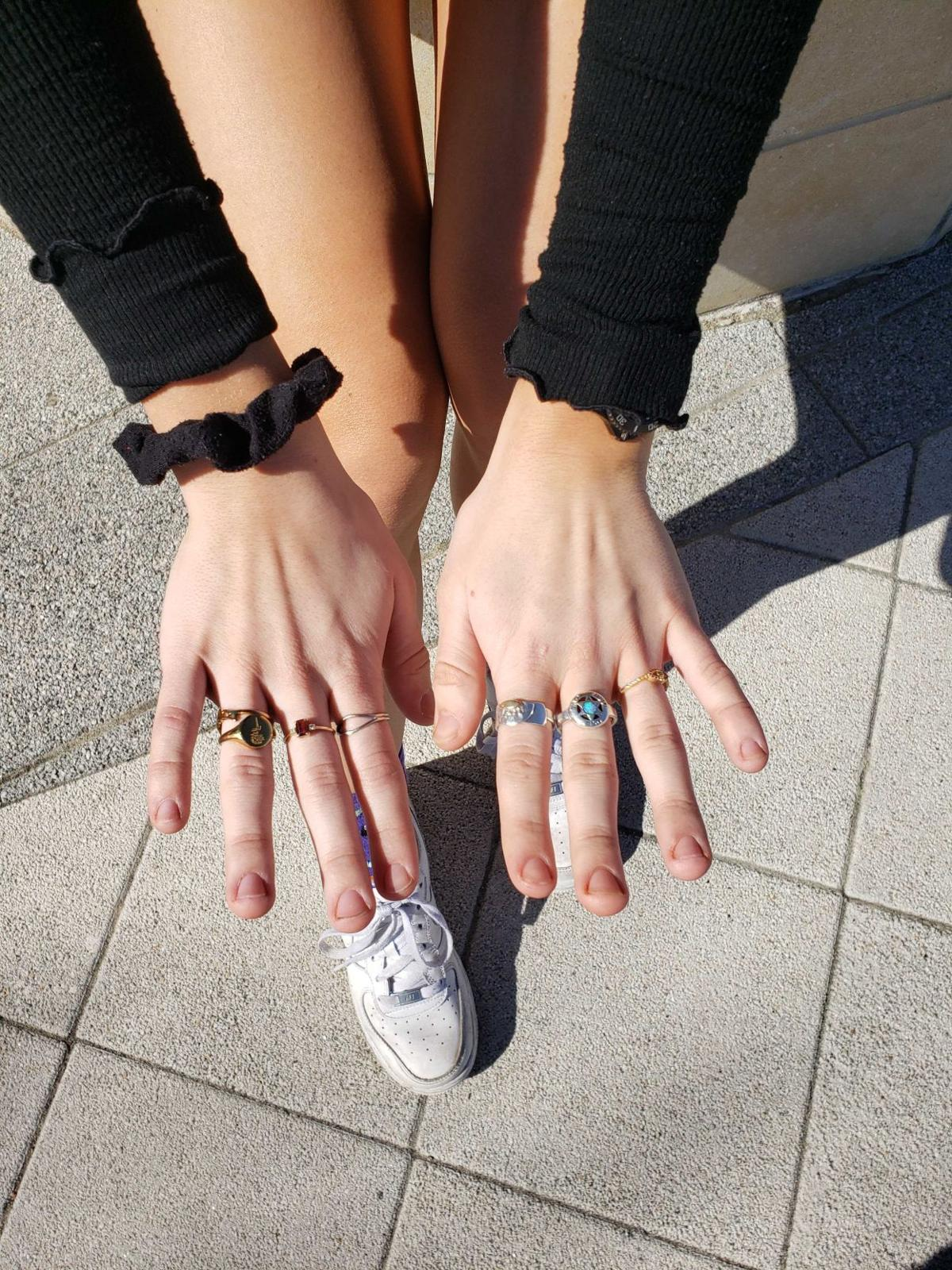 A woman displays several rings on her fingers