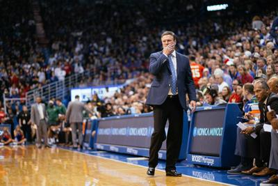 Kansas men's basketball coach Bill Self stands on the sidelines with his right hand holding his face in concern.