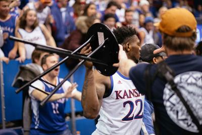 Silvio De Sousa holds a chair above his shoulder during a fight behind the basket.
