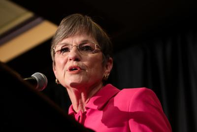 Laura Kelly speaks into the microphone at a podium