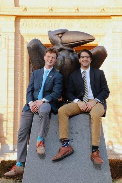 Grant Daily sits next to Apramay Mishra on the Jayhawk statue in front of Strong Hall