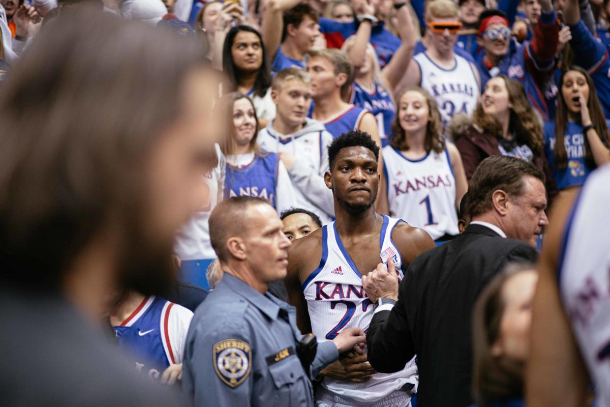 Silvio De Sousa is pulled by the jersey by Bill Self following a fight between players on the court.