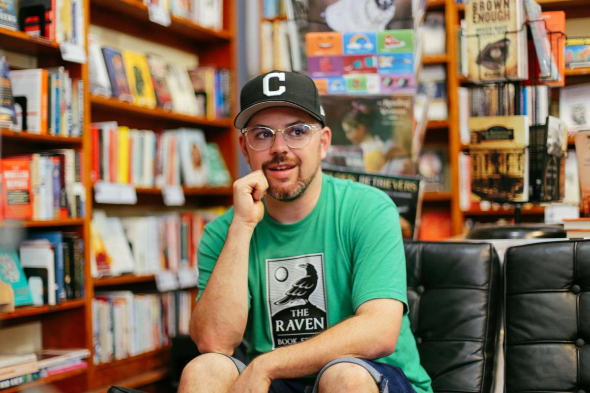 Danny Caine sits with his right fist holding his chin amid the bookshelves of The Raven Book Store