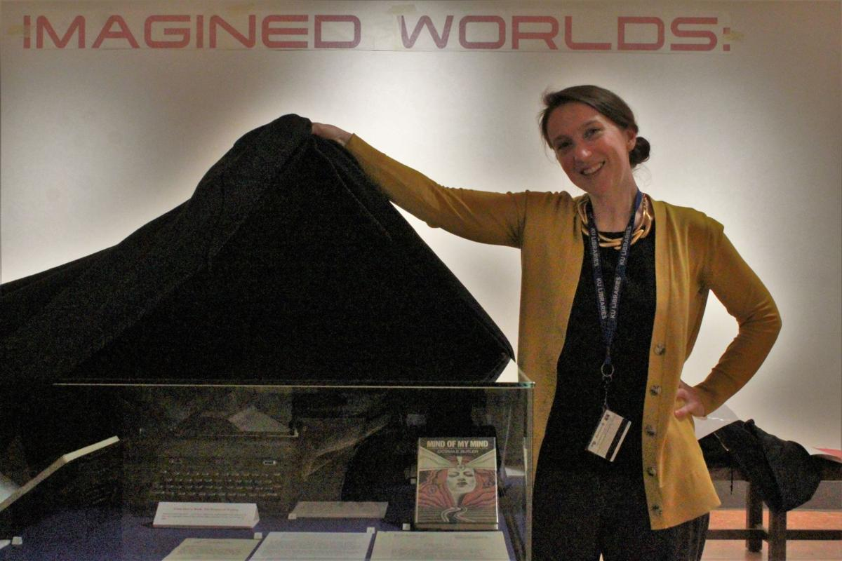 Elspeth Healey unveils a glass case from the Spencer Research Library's newest exhibit 'Imagined Worlds.'