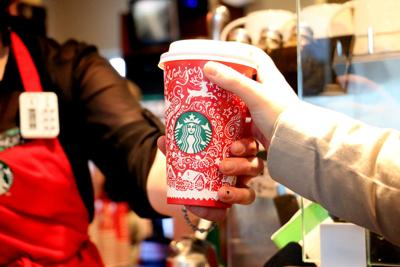 A Starbucks barista hands a customer a reindeer-themed coffee cup