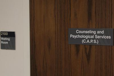 A wood door to Watkins Room 2100 has a sign that reads 'Counseling and Psychological Services (C.A.P.S.)