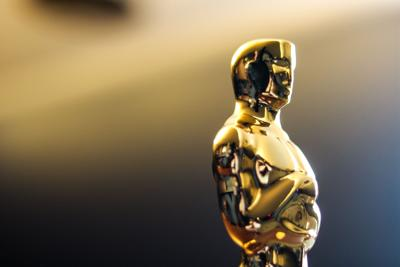 An Oscar statue stands in the foreground shining in light from the right