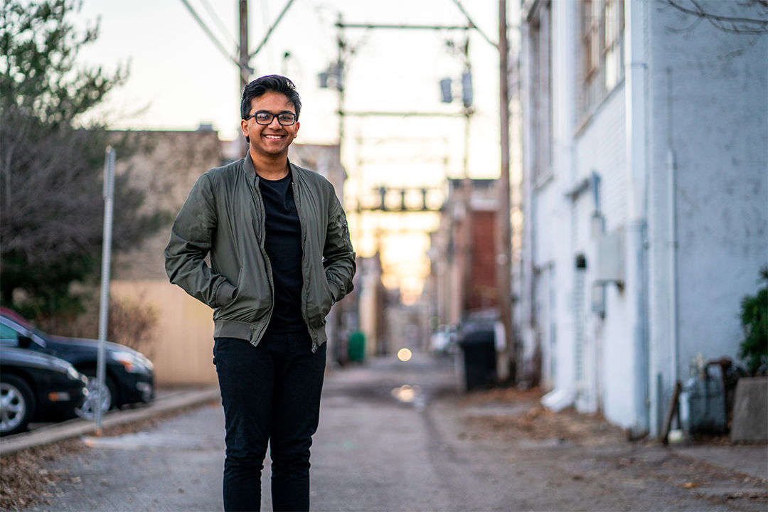 K.U. sophomore Ryan Reza smiles for a photo in an alley behind Massachusetts Street.