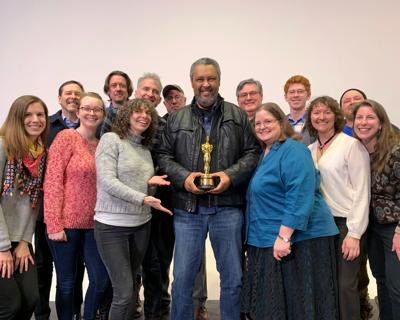 A group of faculty members stand by Kevin Willmott, who holds his Academy Award in the center