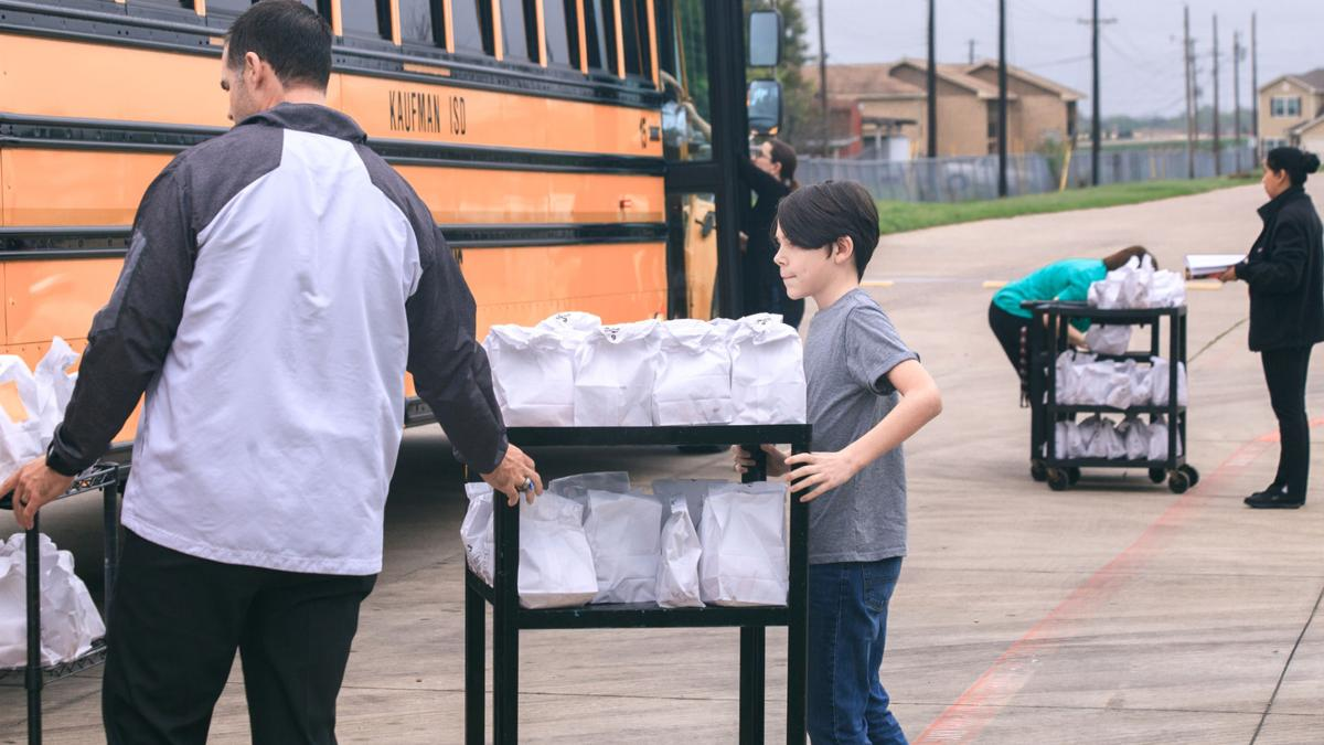 Kell Clopton, left, assistant superintendent at KISD, and volunteers from Kaufman Church of Christ load lunches on Monday. Each bus carried between 92 to 135 lunches to children who live along 29 bus routes in the district.