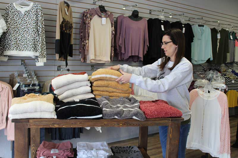 """b1c82677e2b Lillie Kate Boutique owner Melanee Nixon organizes women s sweater s in her  Broken Bow store. Nixon offers """"from babies to grandmas"""" clothing options."""