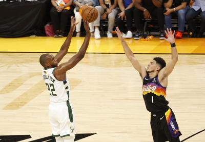 The Milwaukee Bucks' Khris Middleton puts up a shot against the Phoenix Suns' Devin Booker during the first half in Game 1 of the NBA Finals at Phoenix Suns Arena on July 6, 2021 in Phoenix.