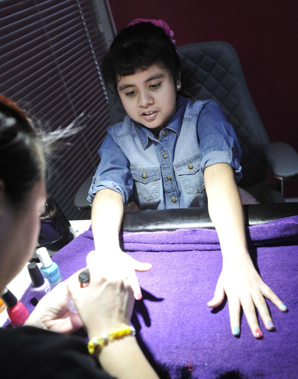 Sofia Matias, 10, gets a manicure from Natalie Curley during the spa day event for children with cancer at Utopia Nails & Spa on Saturday, Feb. 24, 2018.