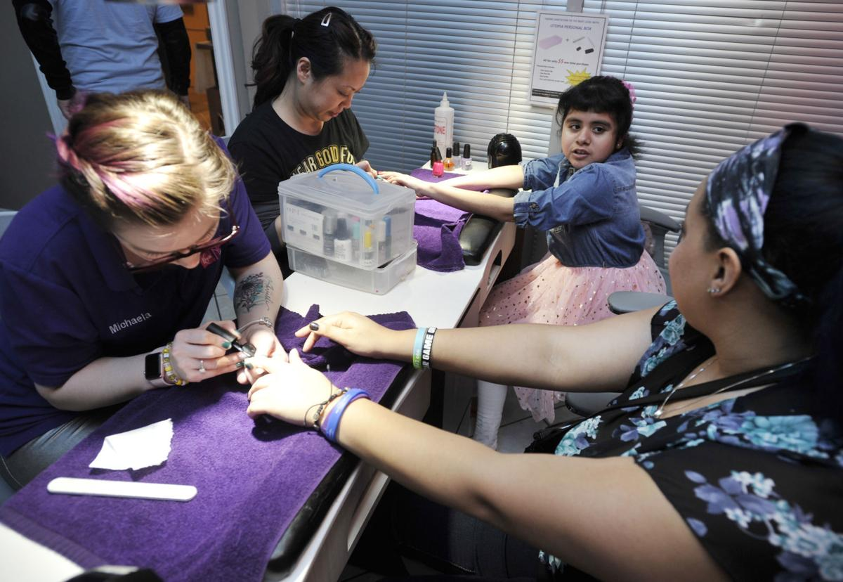Sofia Matias, 10,top right, talks with her sister, Alex Ulloa, bottom right, during the spa day event for children with cancer at Utopia Nails & Spa on ...