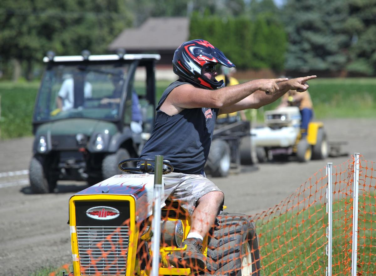 Jimmy Mueller, of Muskego, points at the crowd after being the first, and only, to make a full pull in the 1,000-pound adult class during the garden tractor ...